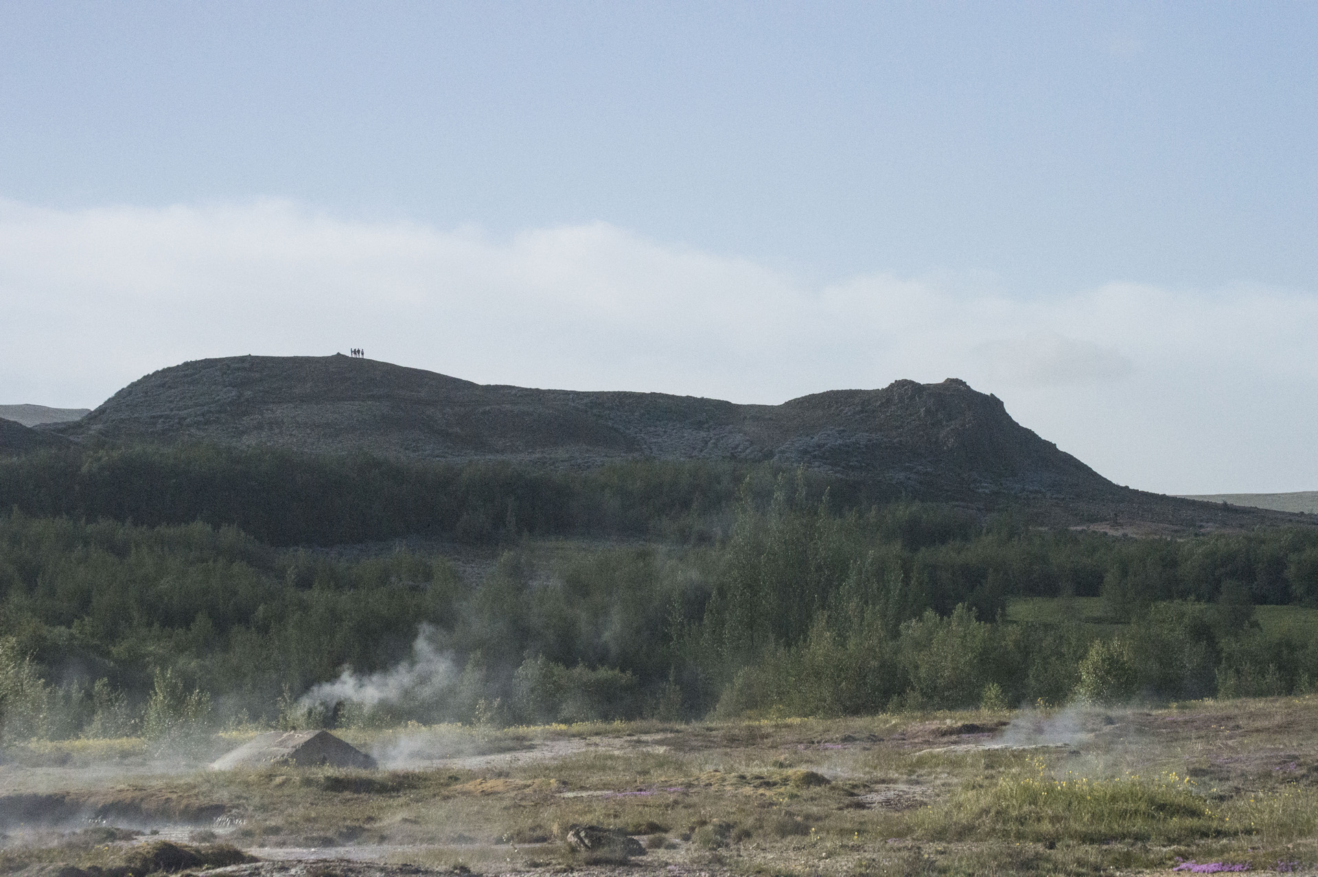 A steam hut in front of one of the bluffs that surround the Geysir Hot Spring Area in the Haukadalur Valley, Iceland.