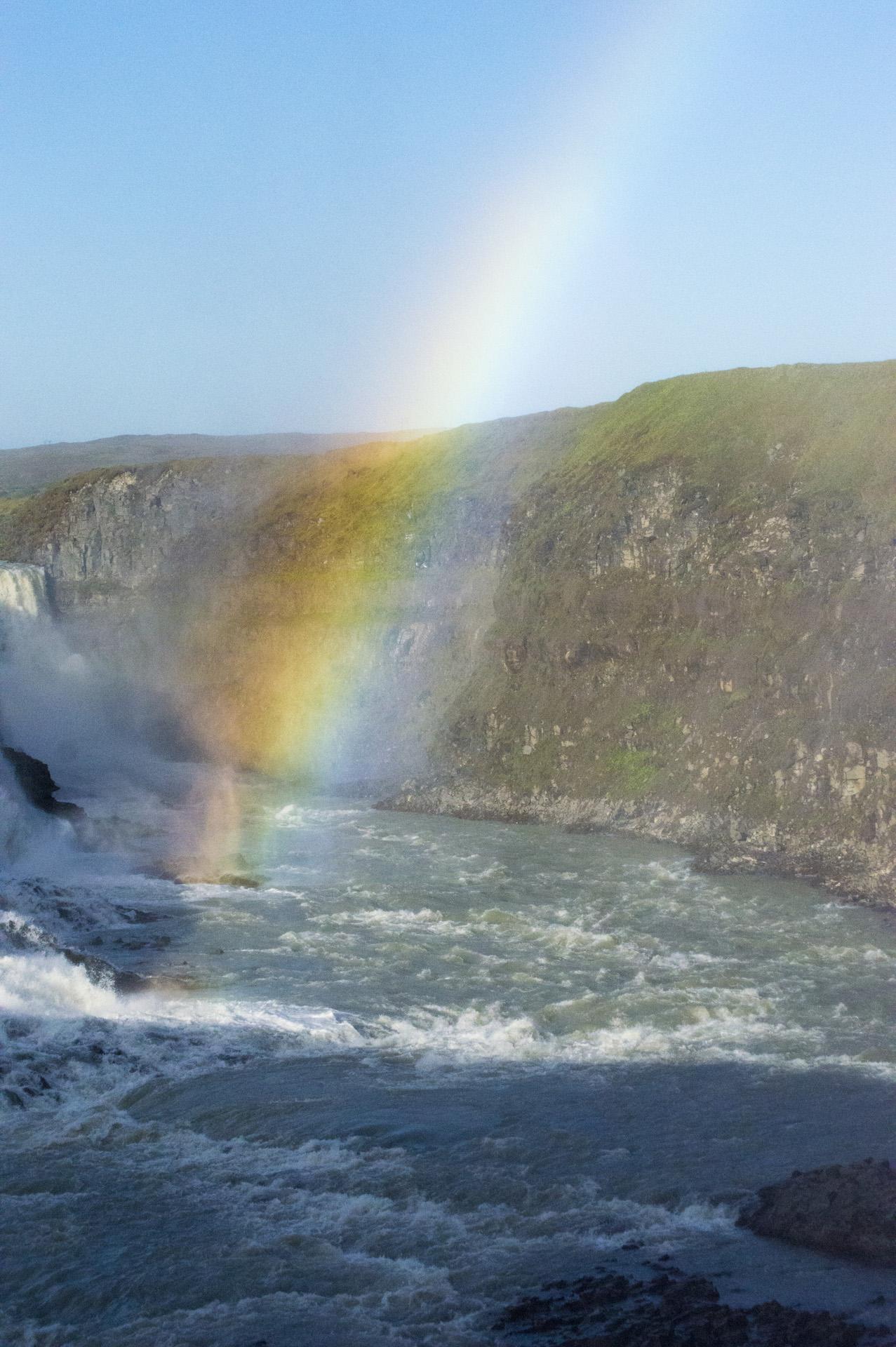 Rainbow extends from Gullfoss waterfall, Suðurland region, Iceland