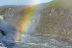 Rainbow extends from Gullfoss waterfall, Suðurland region, Iceland